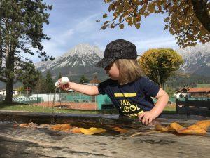 Merlin spielt mit Wasser vor der Bergkulisse in Ellmau