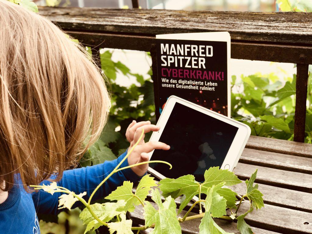 Merlin spielt auf dem Tablet, dahinter steht das Buch Cyberkrank von Marin Spitzer