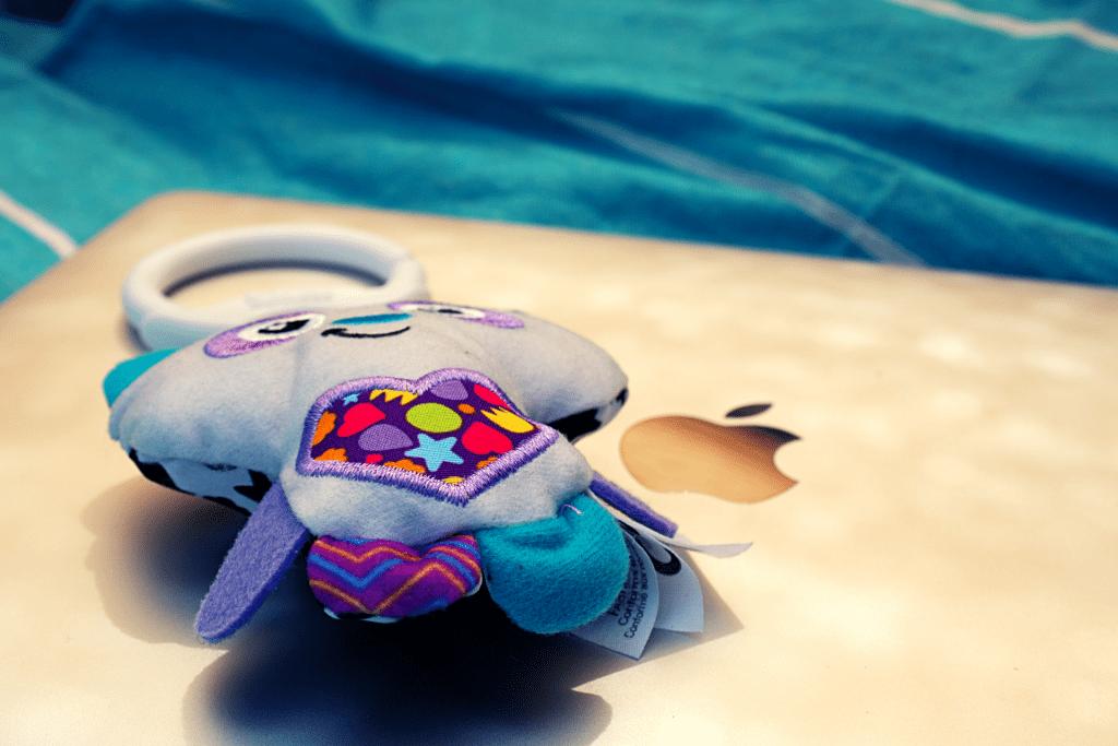 Macbook pro auf Gartenliege mit Babyspielzeug