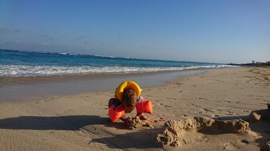 Langzeitreisen mit Kind – Kind spielt am Strand.