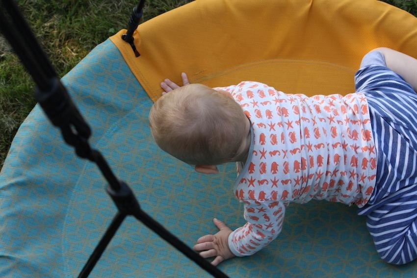 Kleinkind krabbelt auf Nestschaukel