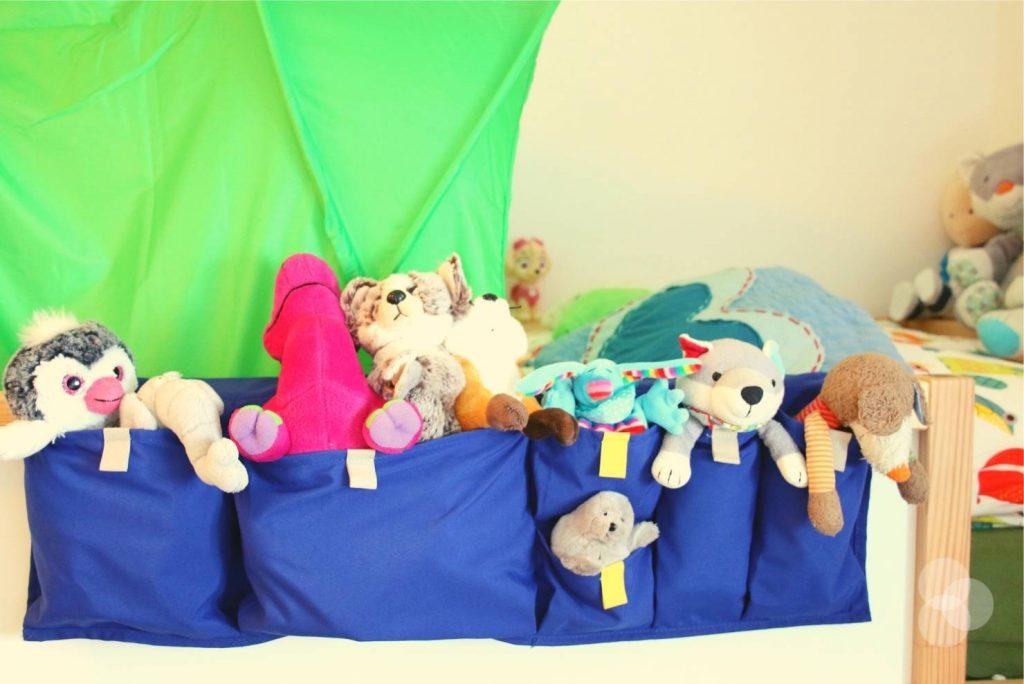 Kinderzimmer Aufbewahrung in blau am Bett mit Kuscheltieren